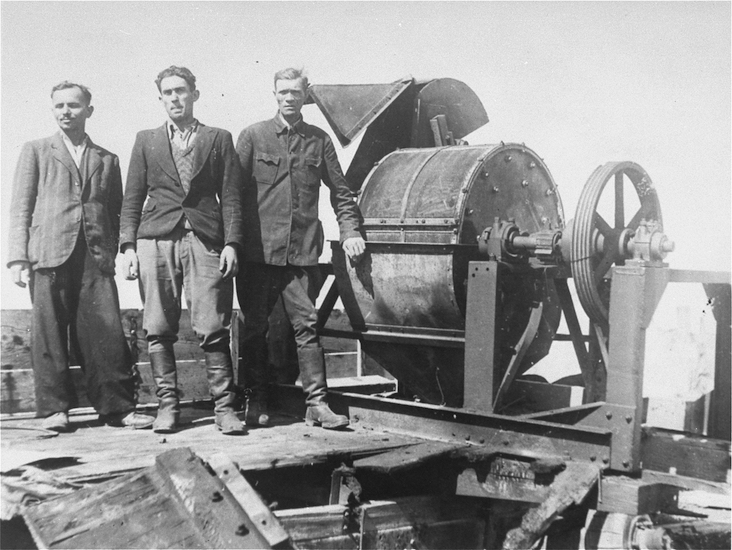 Jewish prisoners forced to work for a Sonderkommando 1005 unit pose next to a bone crushing machine in the Janowska concentration camp. Pictured from left to right are: unknown, David Manusevitz, and Moses Korn.
