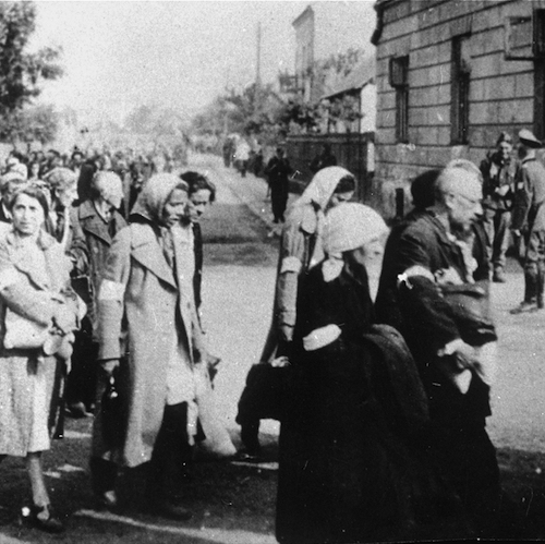 Jews walk in a long column through the streets of Rzeszow during a deportation action from the ghetto. July 1942